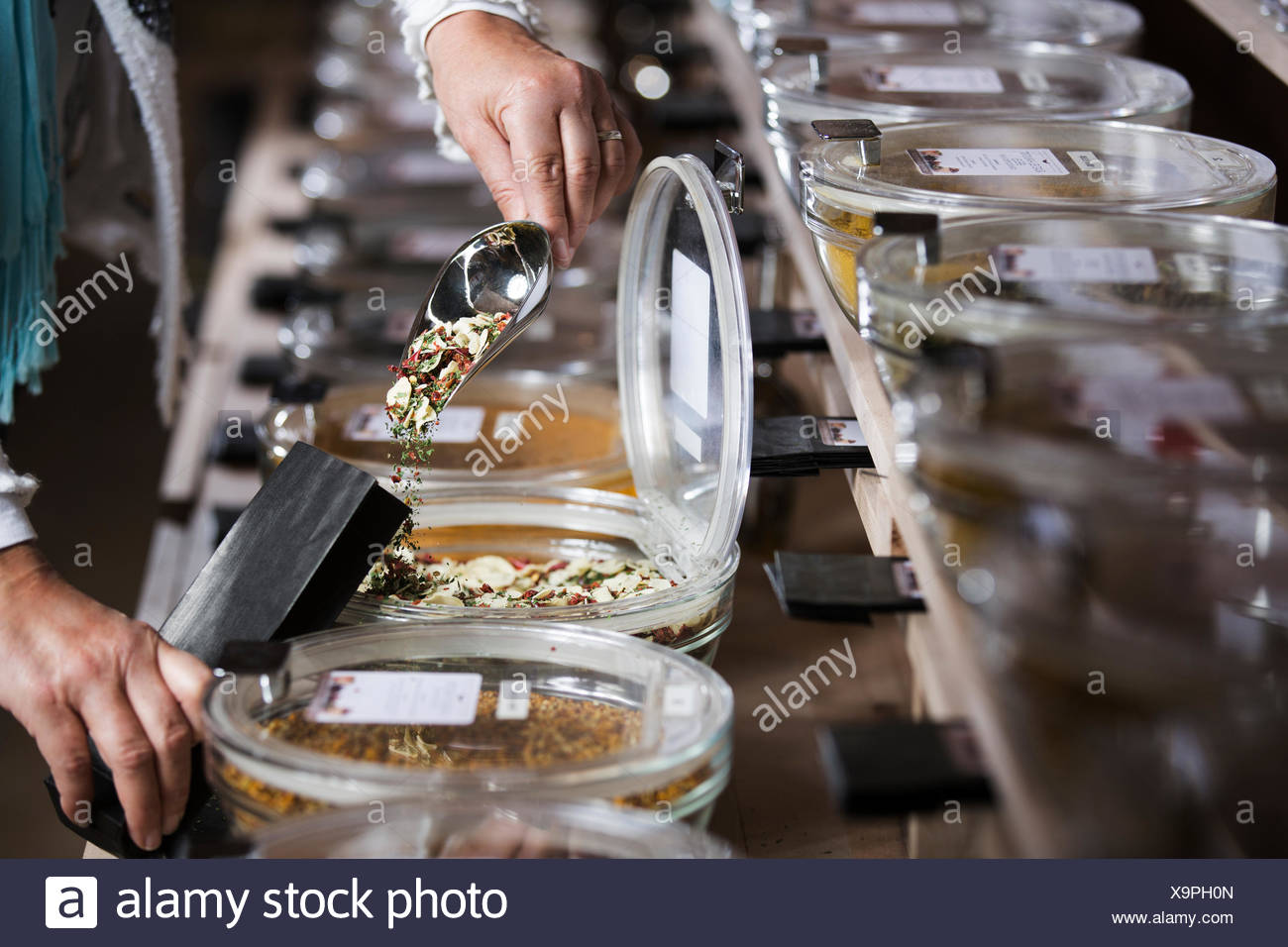 Spice mixture being poured into paper bag, dried garlic, parsley, paprika, chilli, basil and oregano - Stock Image