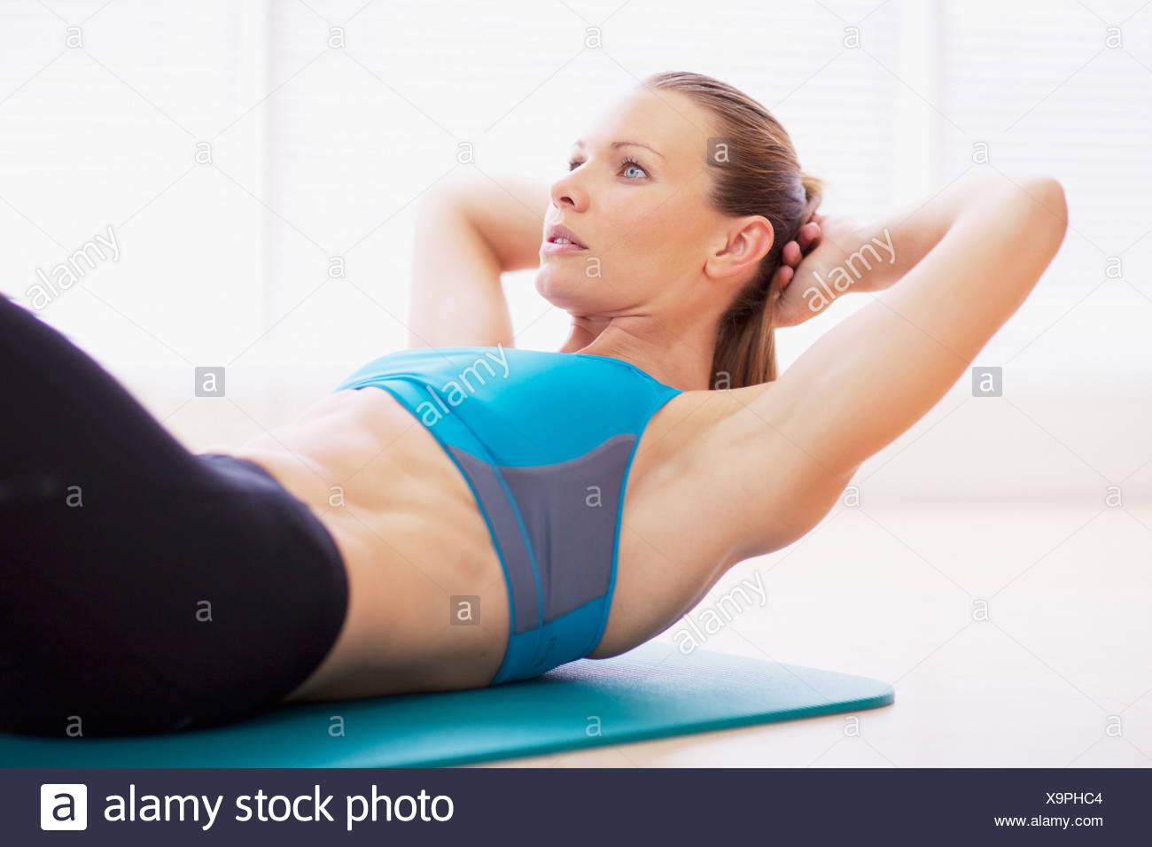 Serious woman in sports bra doing sit-ups on exercise mat Stock Photo