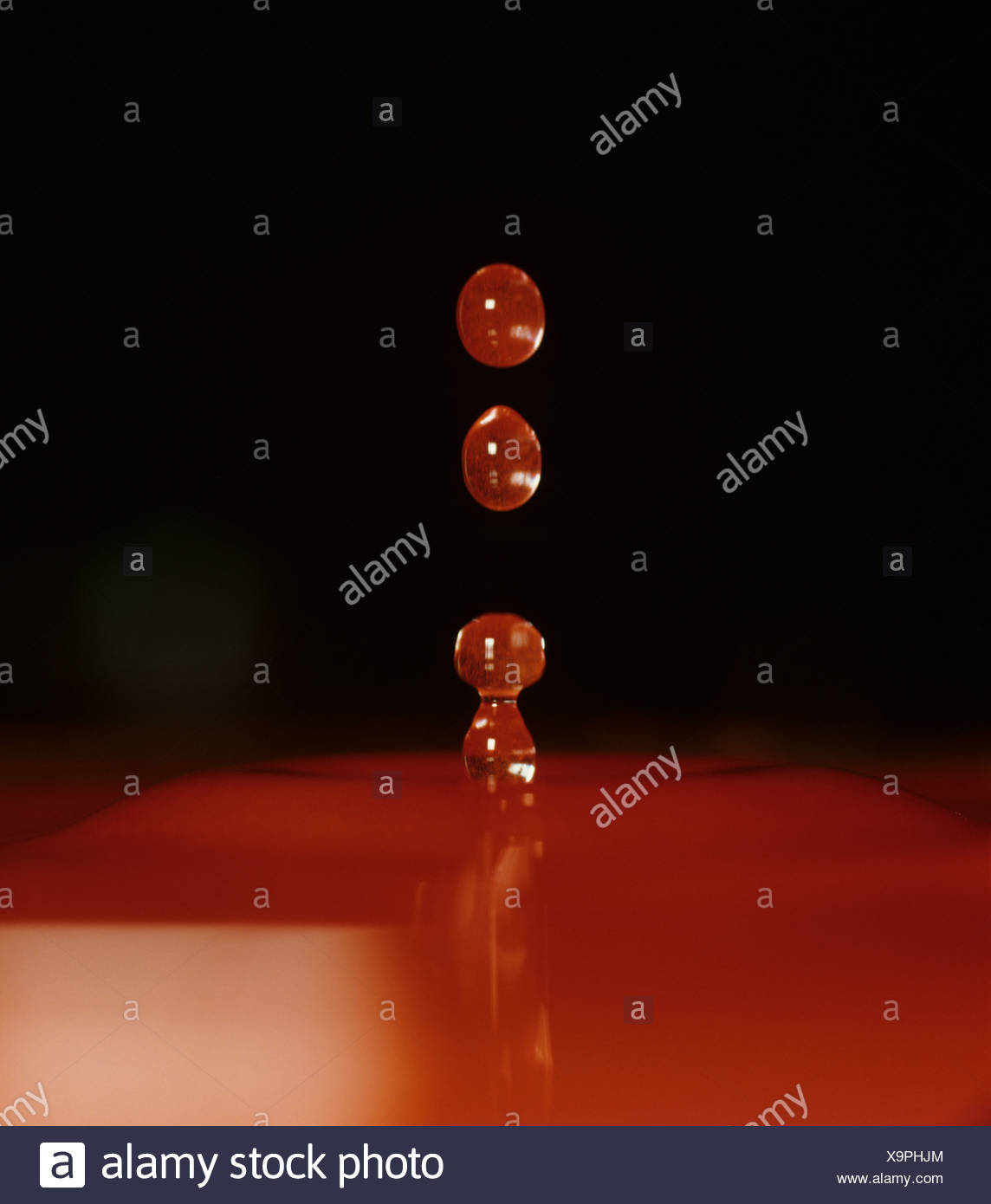 A column splash of red dyed water breaking up as it falls back - Stock Image