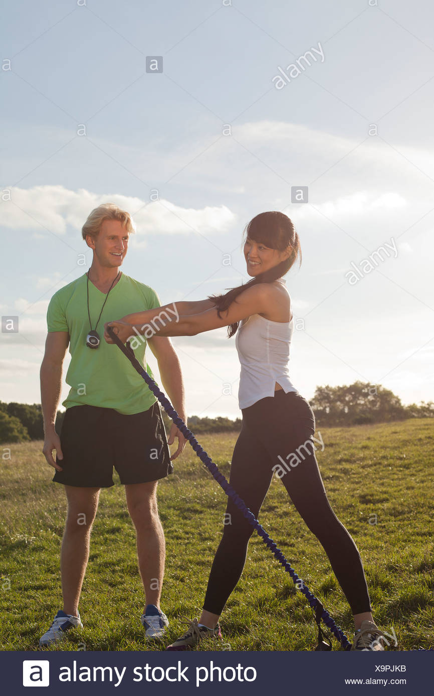 Personal trainer and female client doing stretch exercise - Stock Image