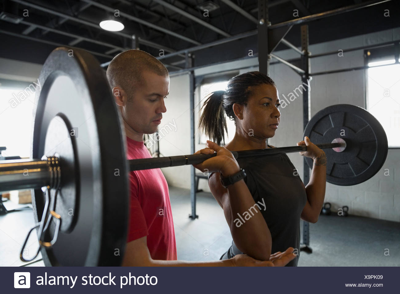 Personal trainer guiding woman weightlifting barbell Stock Photo