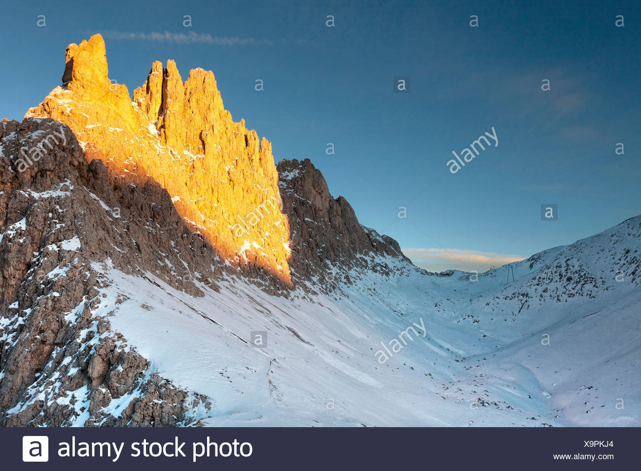 Santnerpass and Croda of King Laurin (Croda di Re Laurino) in a sunlit morning in early winter. Snow covers the entire path to the Santner pass, Rosengarten group - Catinaccio, Dolomites - Stock Image