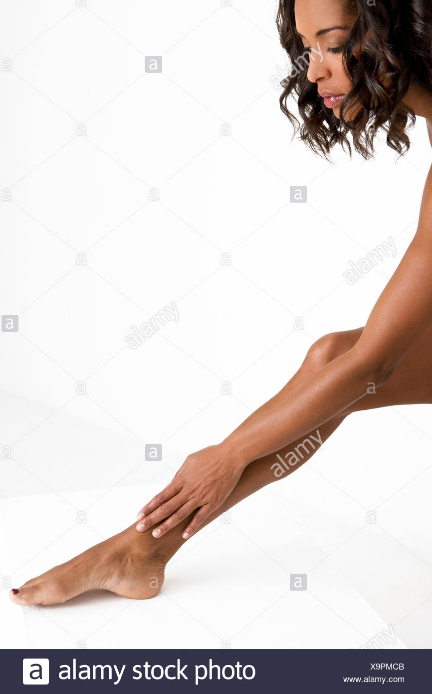 A woman rubbing her lower leg - Stock Image