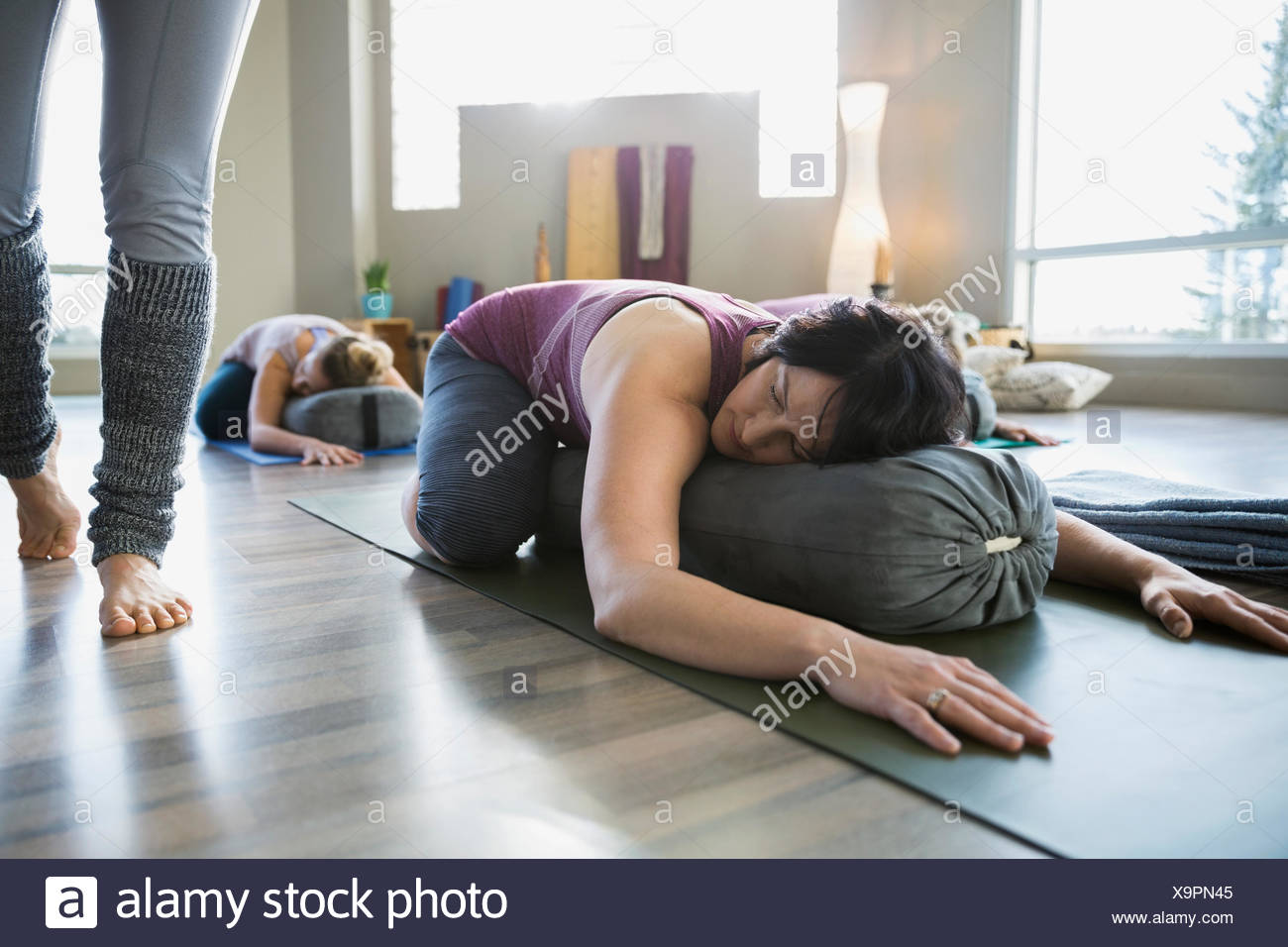 Woman using bolster in restorative yoga childs pose Stock Photo