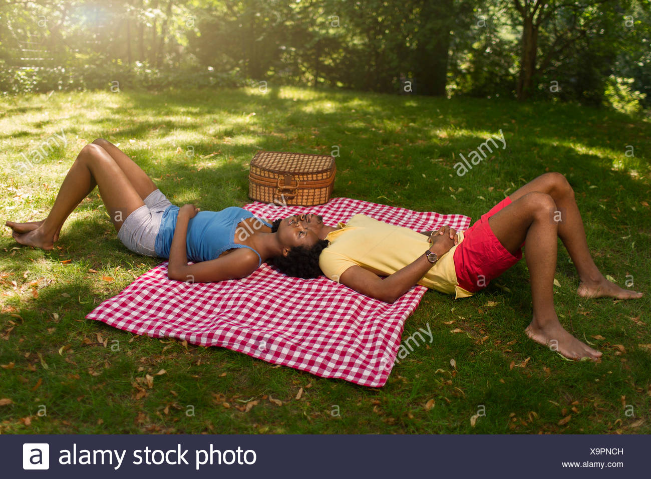 Young couple lying on picnic blanket in park on opposite sides - Stock Image