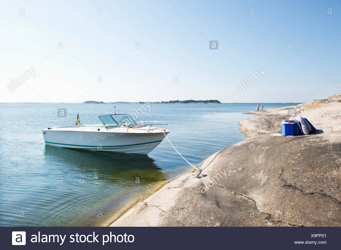 Moored motor boat at sunny day and tourists (4-5, 12-13) on background - Stock Image