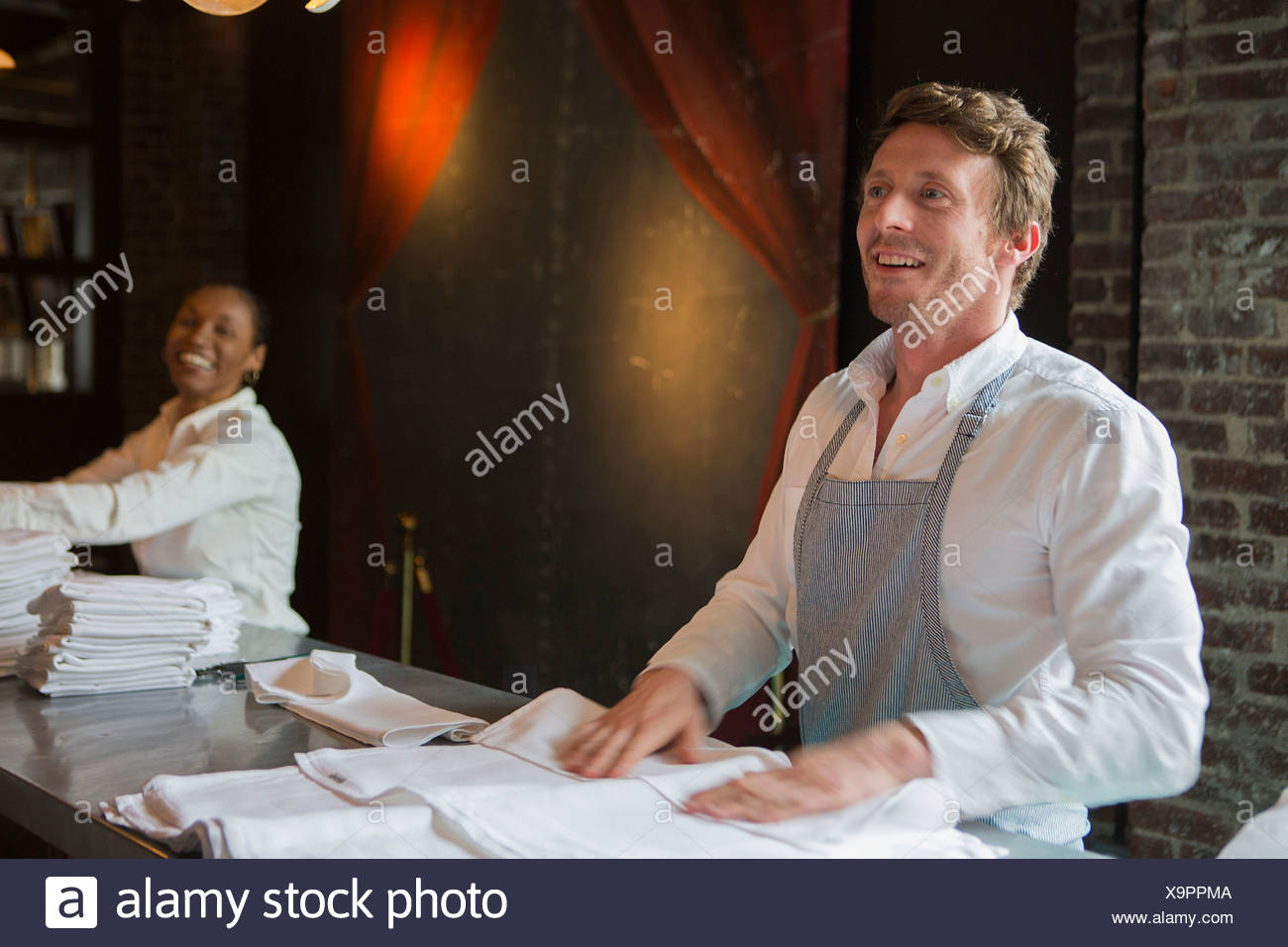 Chef and waitress folding napkins in restaurant - Stock Image
