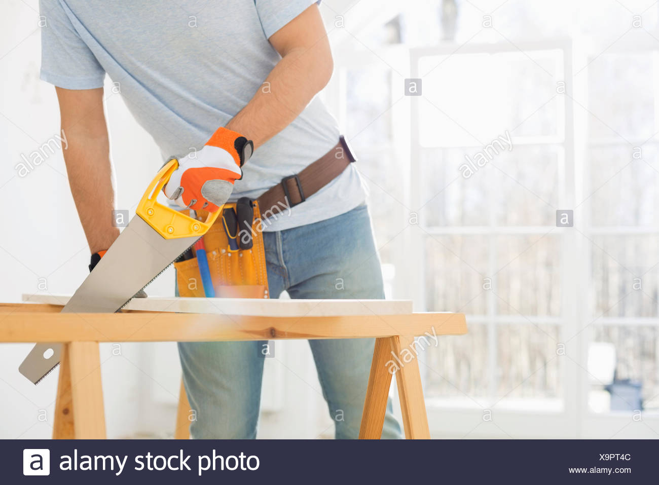 Midsection of man sawing wood in new house - Stock Image