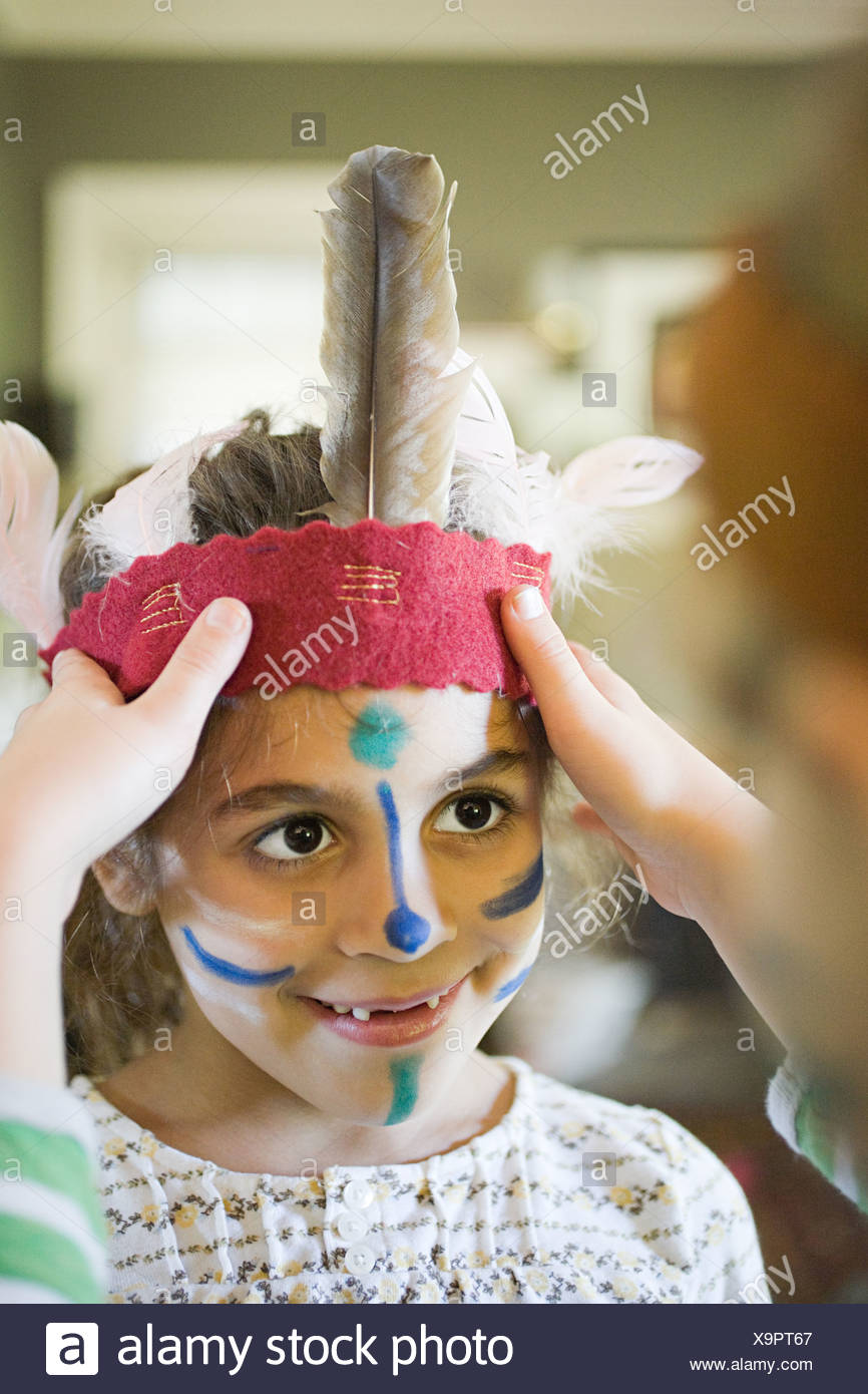 Girl putting Native American headdress on another girl - Stock Image