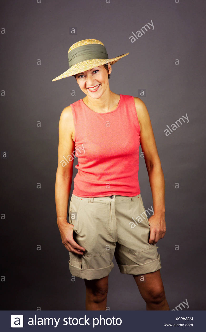 a woman summerly wearing shorts and a strawhat - Stock Image