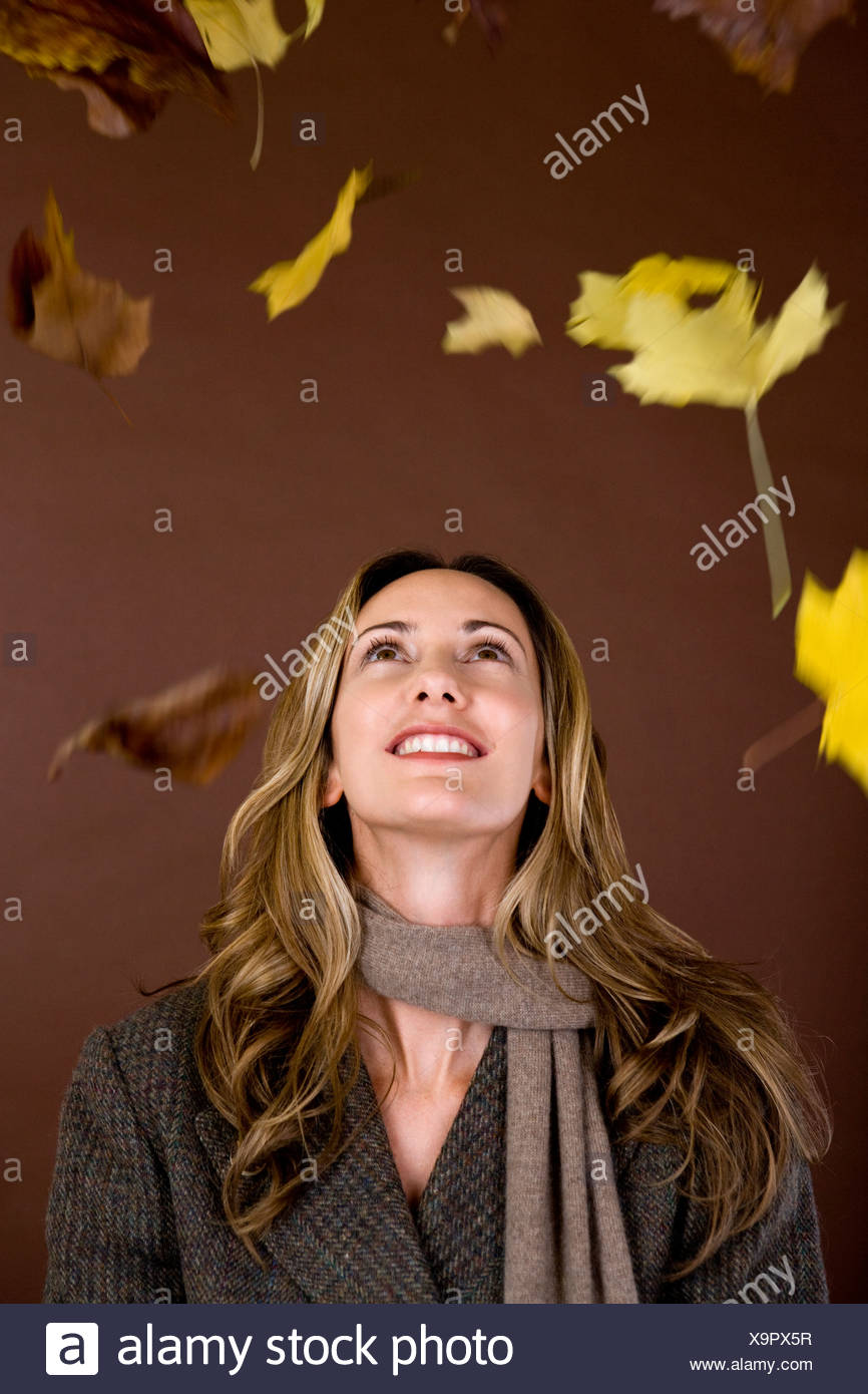 A mid adult woman smiling at falling autumn leaves - Stock Image