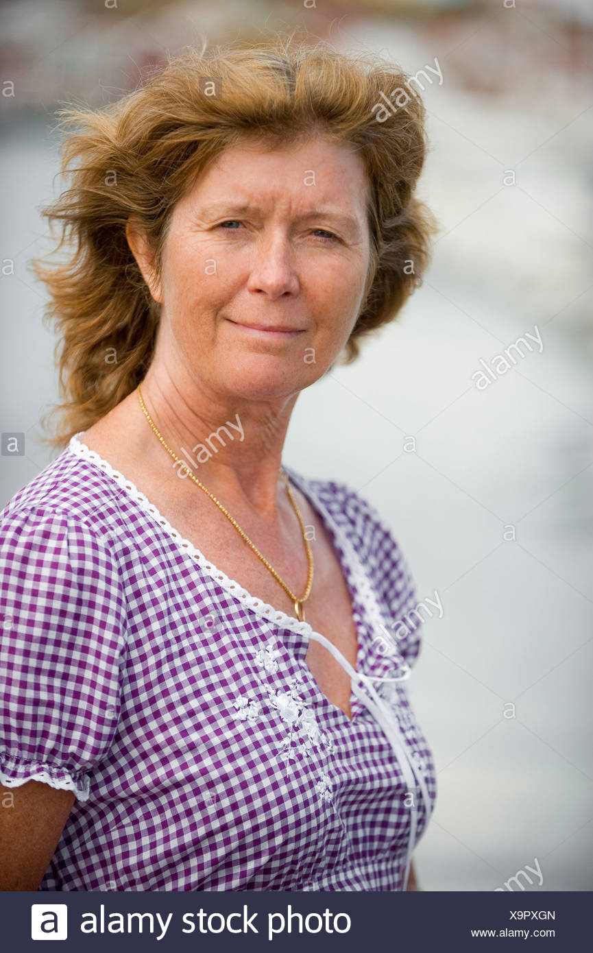 Portrait of a mature woman against blurred background - Stock Image