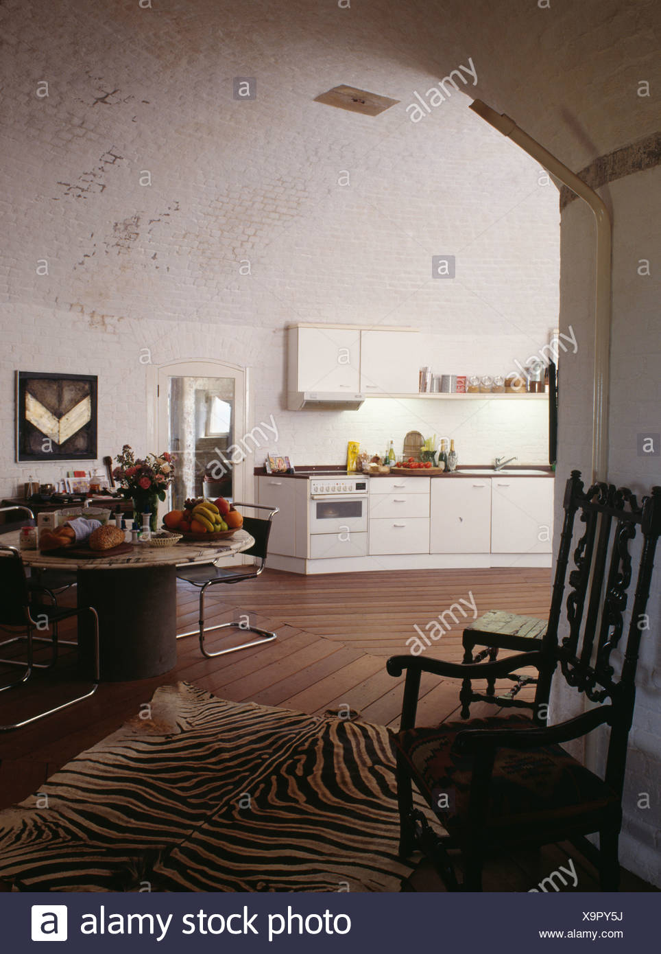 Jacobean chair and old zebra-skin rug in dining area of modern high-ceilinged kitchen in converted Martello Tower Stock Photo