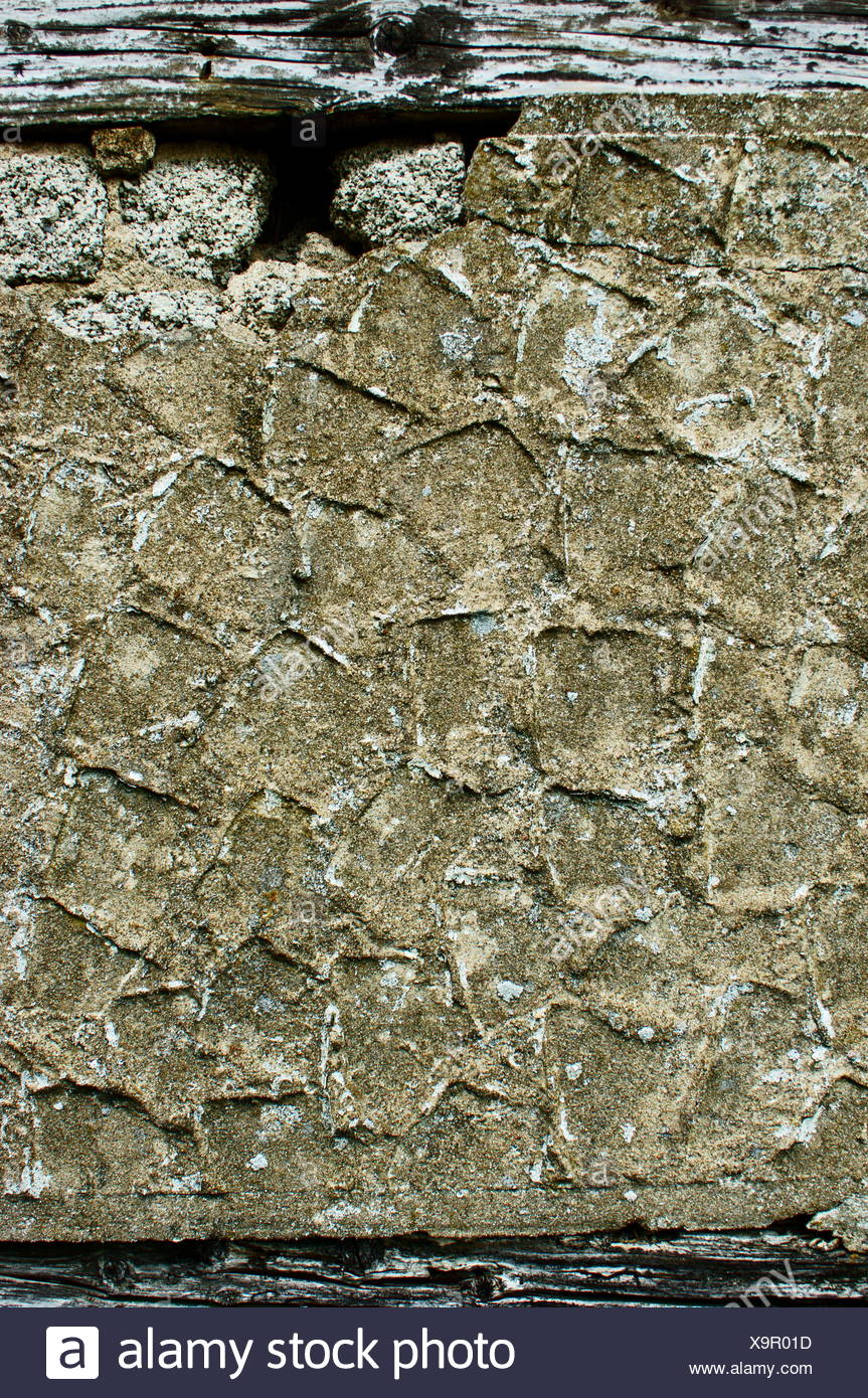 Weathered exterior wall surface with exposed wood - Stock Image