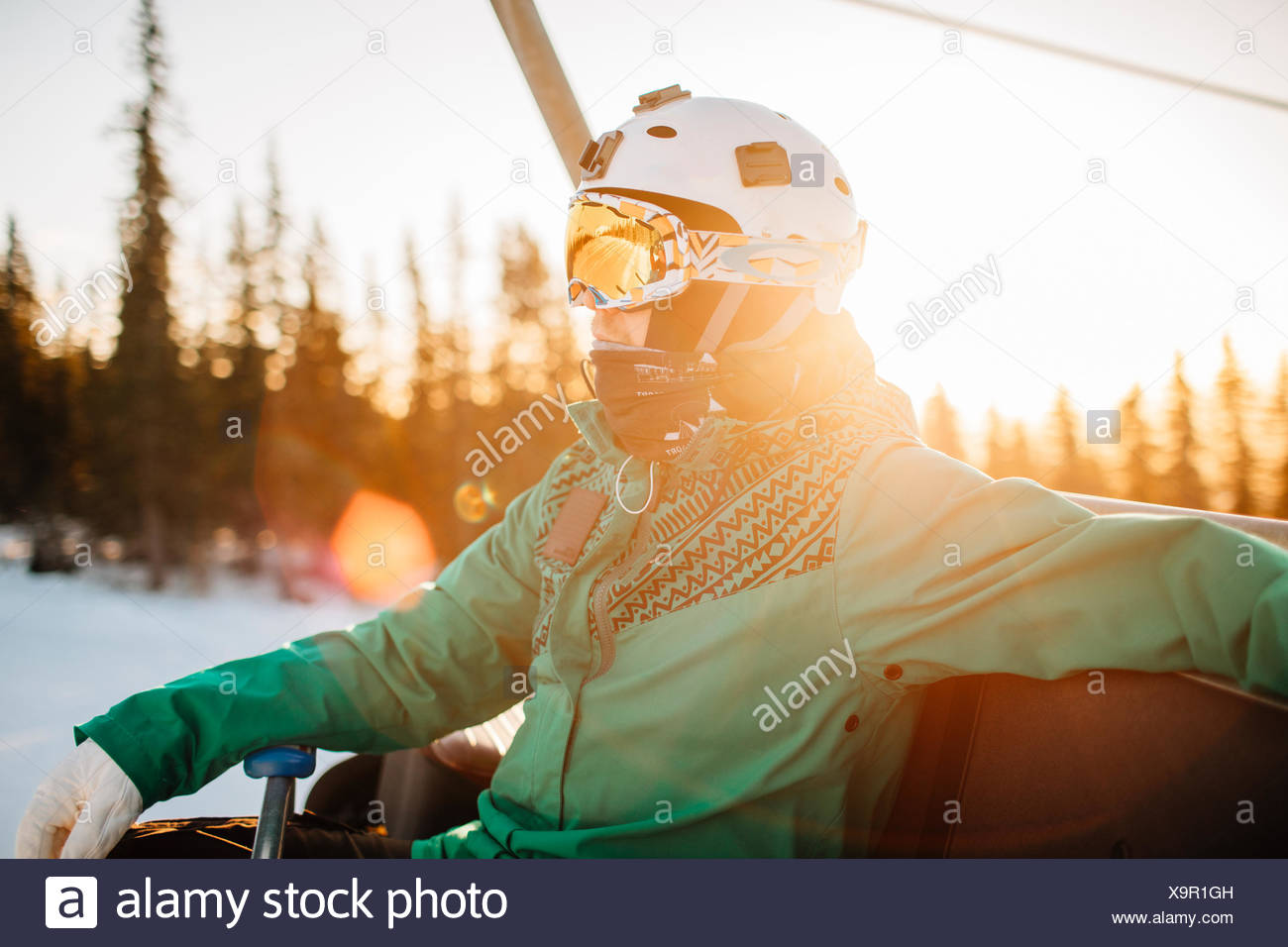 Man wearing goggles and helmet at sunset in Osterdalen, Norway - Stock Image