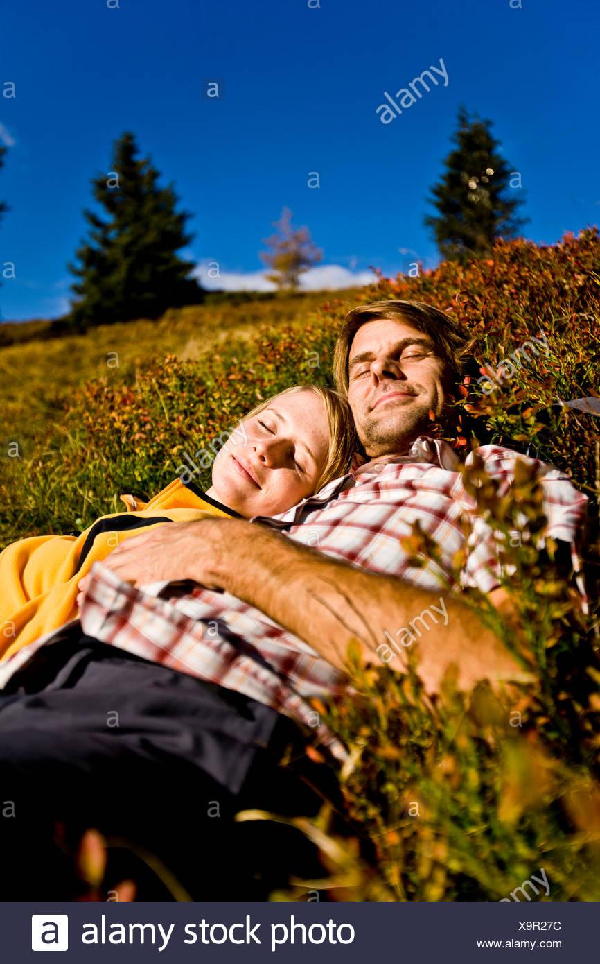 Hikers lying on autumnal alp, Planai, Schladming, Styria, Austria - Stock Image