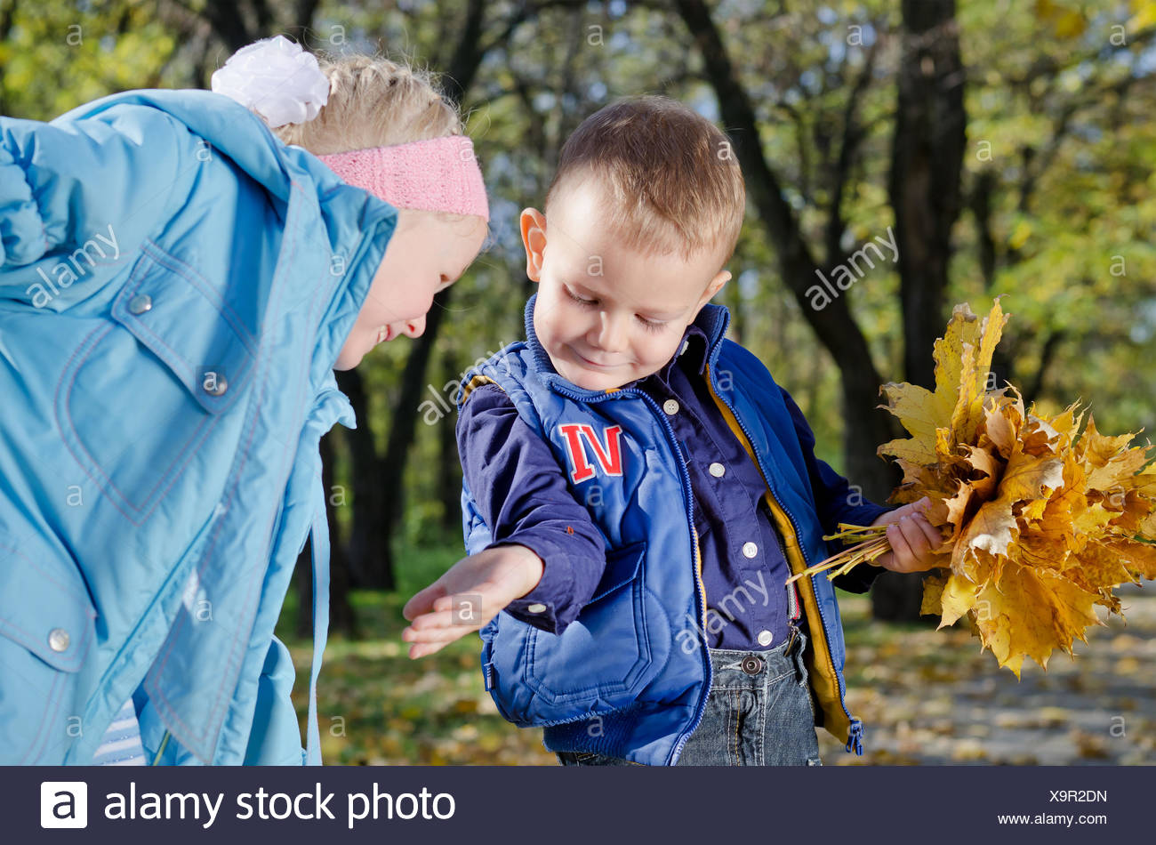 Young Children with Autumn Leaves - Stock Image