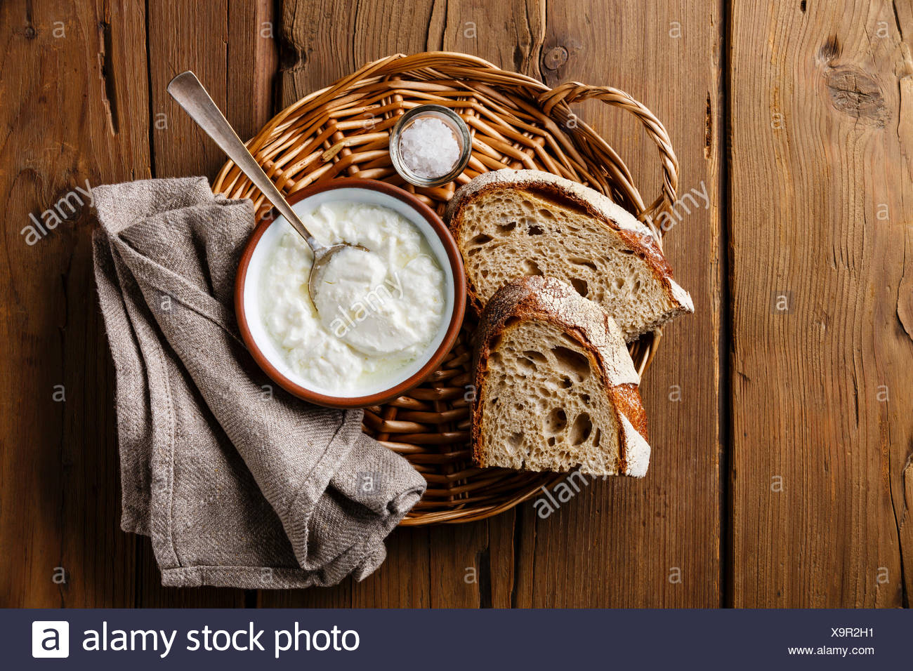 Clabber sour milk and brown rye bread on wicker tray on wooden background - Stock Image