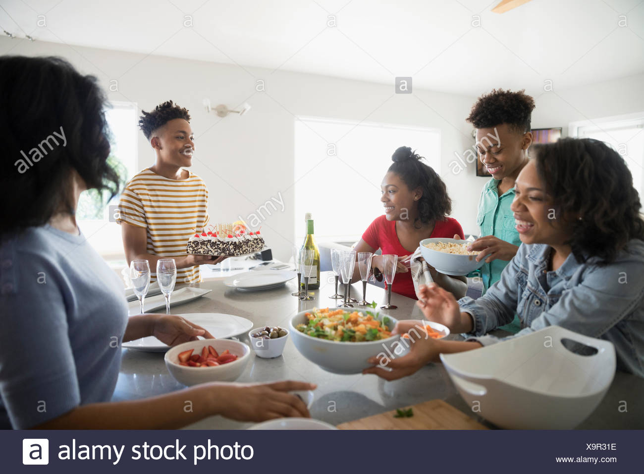 African American family cooking and eating in kitchen - Stock Image