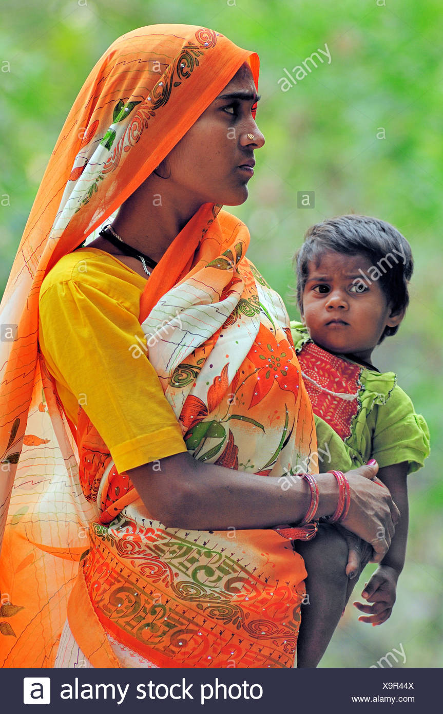 Indian Woman Carrying A Small Child In Her Arms Bharatpur Rajasthan India