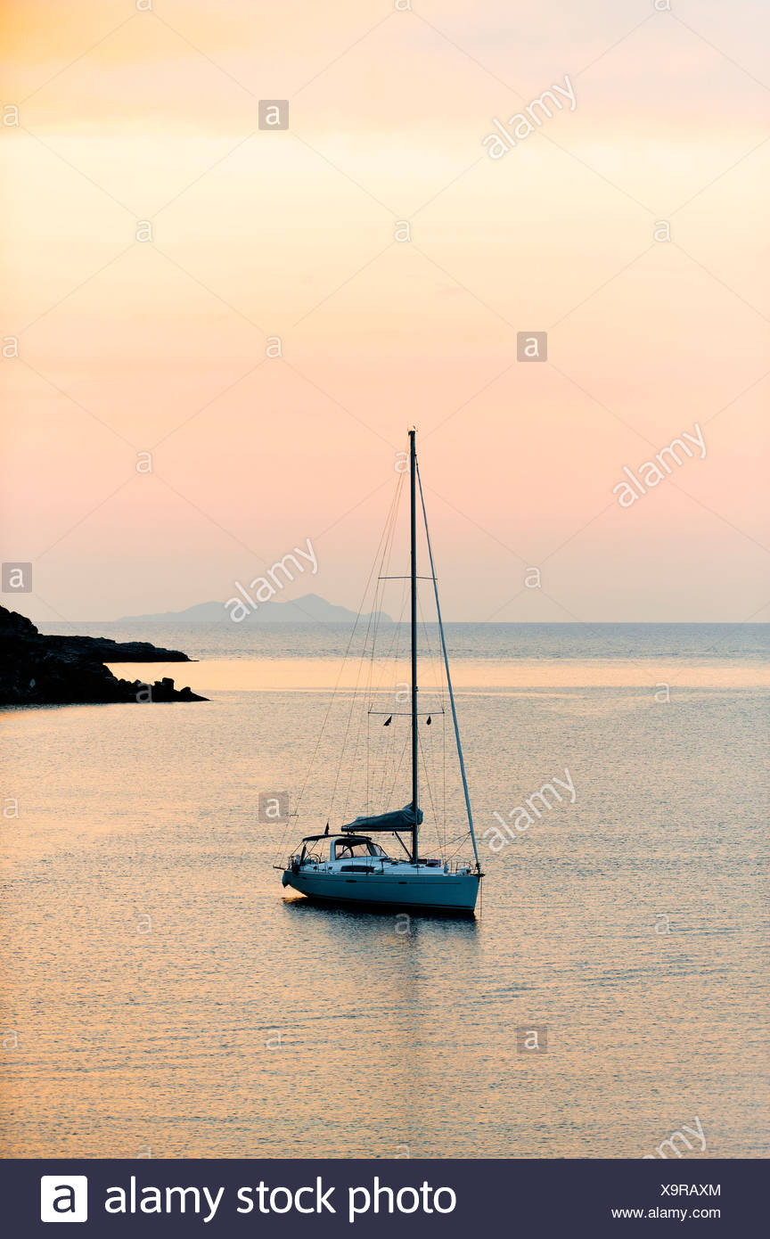 Sailboat anchored in the peaceful water at sunset - Stock Image