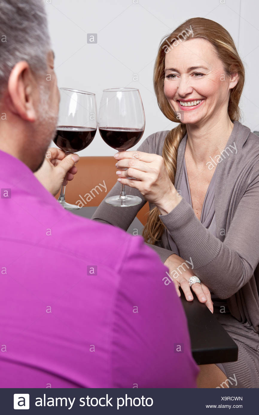 Middle aged people clinking glasses - Stock Image