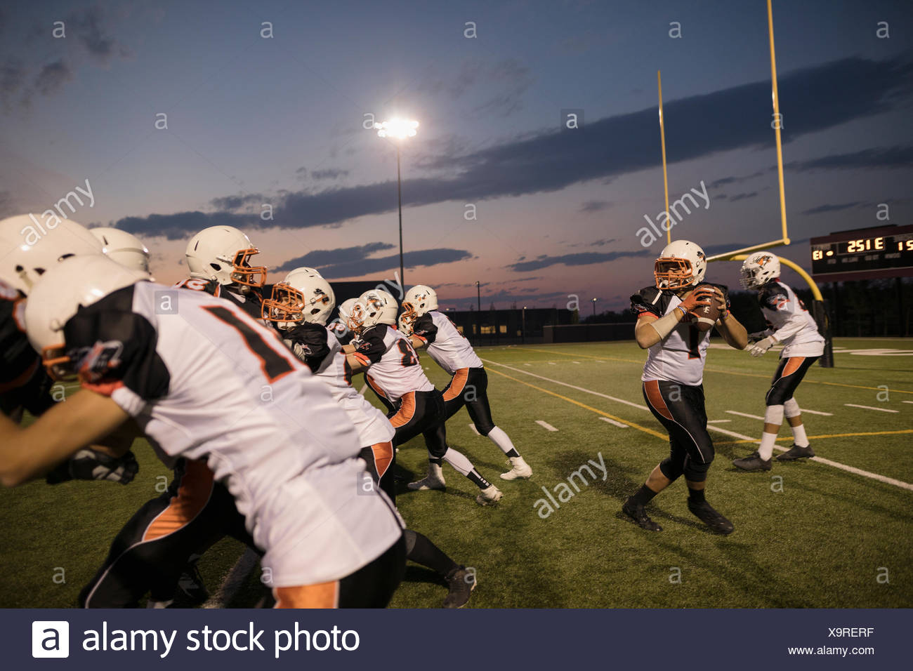 Teenage boy high school football quarterback throwing the ball during game on football field - Stock Image