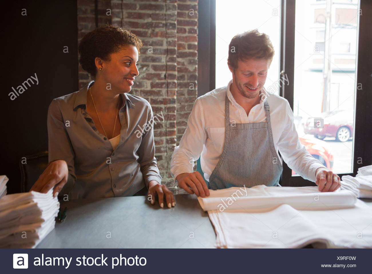 Chef and waitress preparing napkins in restaurant - Stock Image