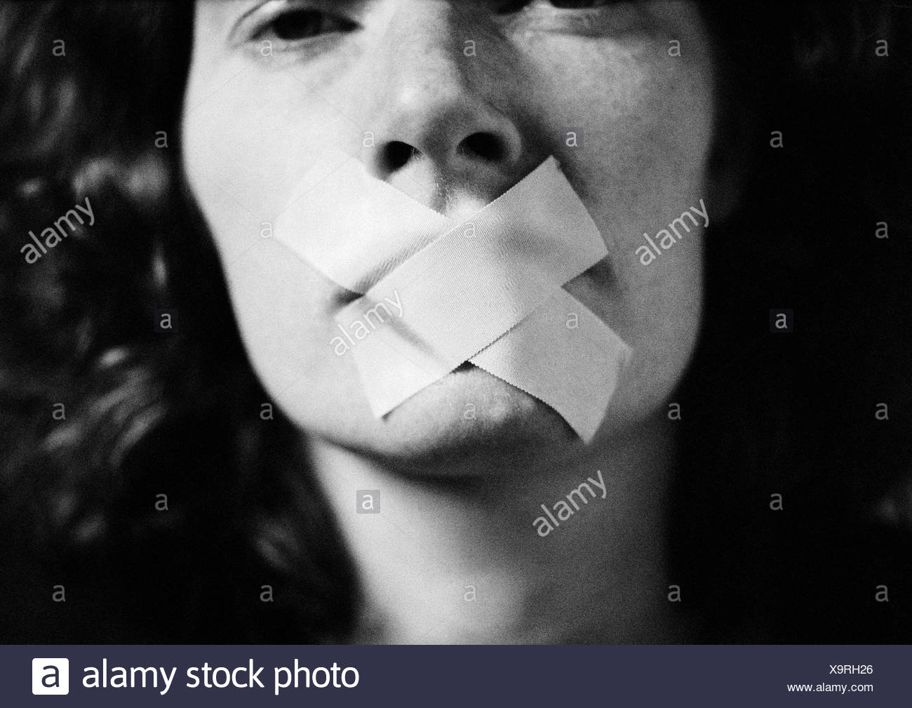 Woman with tape over mouth, close-up, blurred - Stock Image