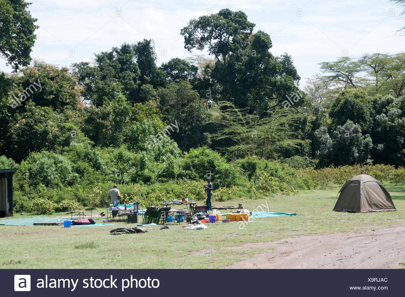 Staff working at striking camp and collecting kit on camp site near Makalia Falls in Lake Nakuru National Park Kenya East Africa - Stock Image