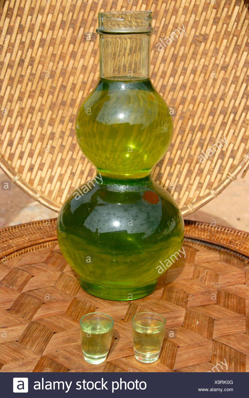 Green Lao Lao, bulbous glass bottle filled with alcohol, Laotian rice liquor, Phongsali, Phongsali province, Laos, Southeast As - Stock Image