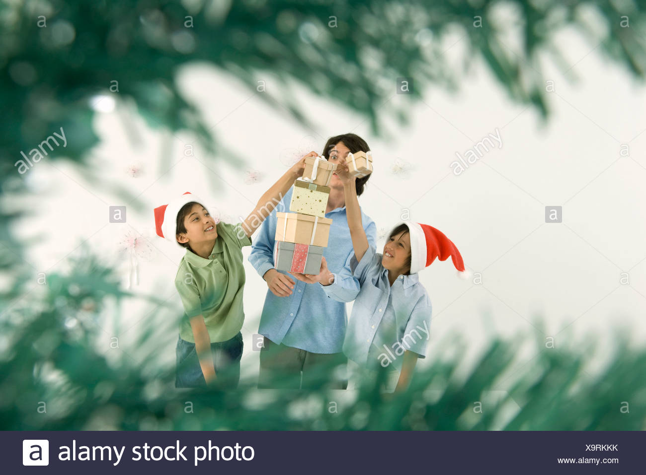 Young man holding tall stack of Christmas gifts, boys placing more ...