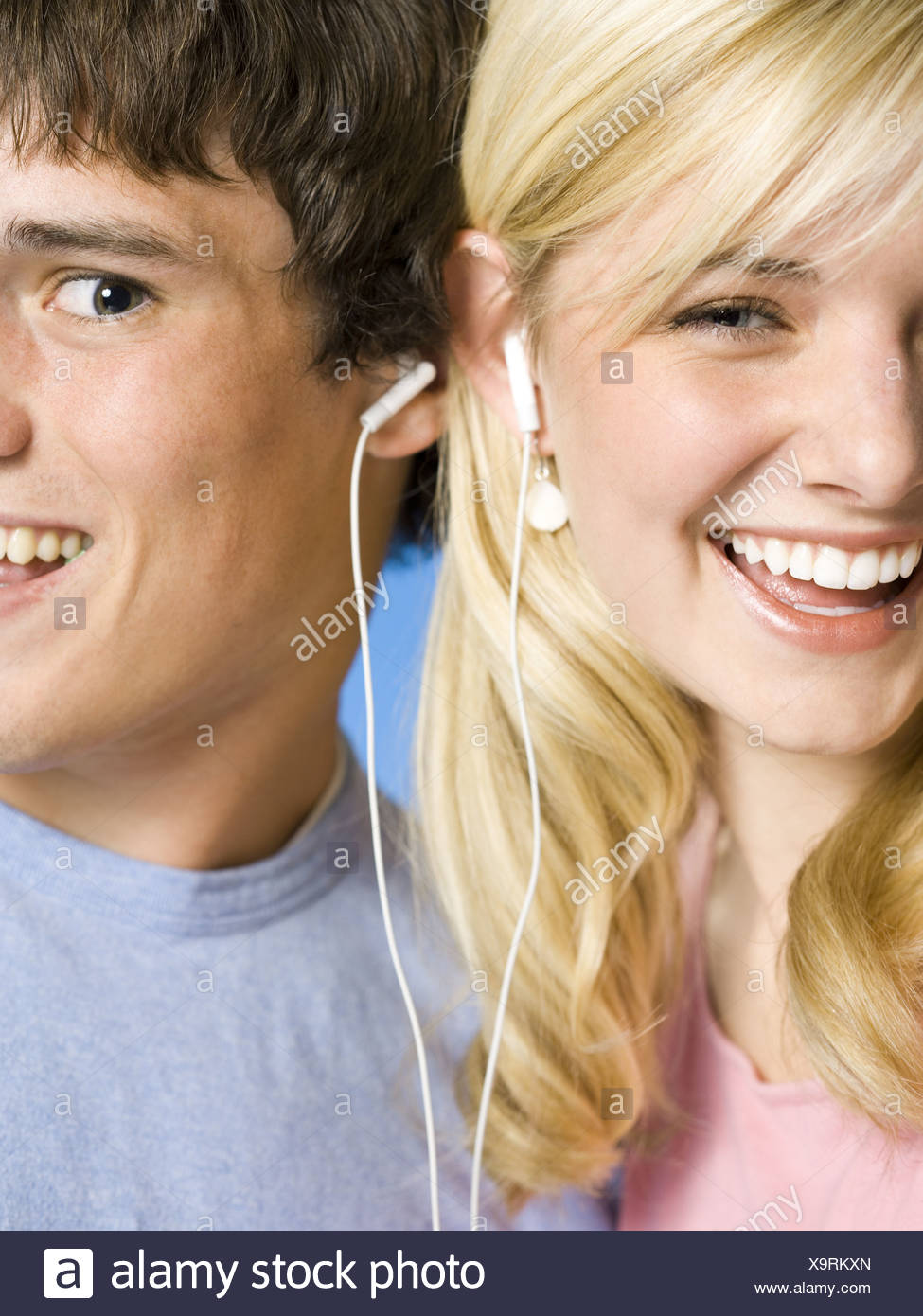 Portrait of a young couple with ear buds smiling - Stock Image