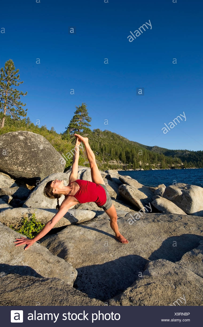 A young woman performs yoga in warm afternoon light on granite boulders on the east shore of Lake Tahoe in the summer, NV. - Stock Image