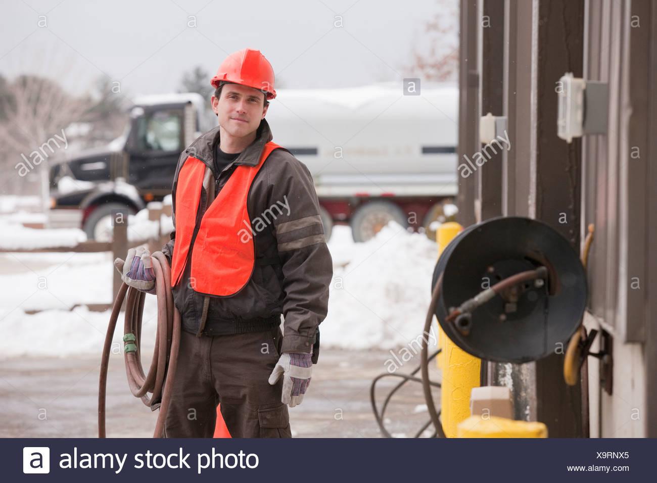 Transportation engineer unrolling hose at an industrial garage - Stock Image