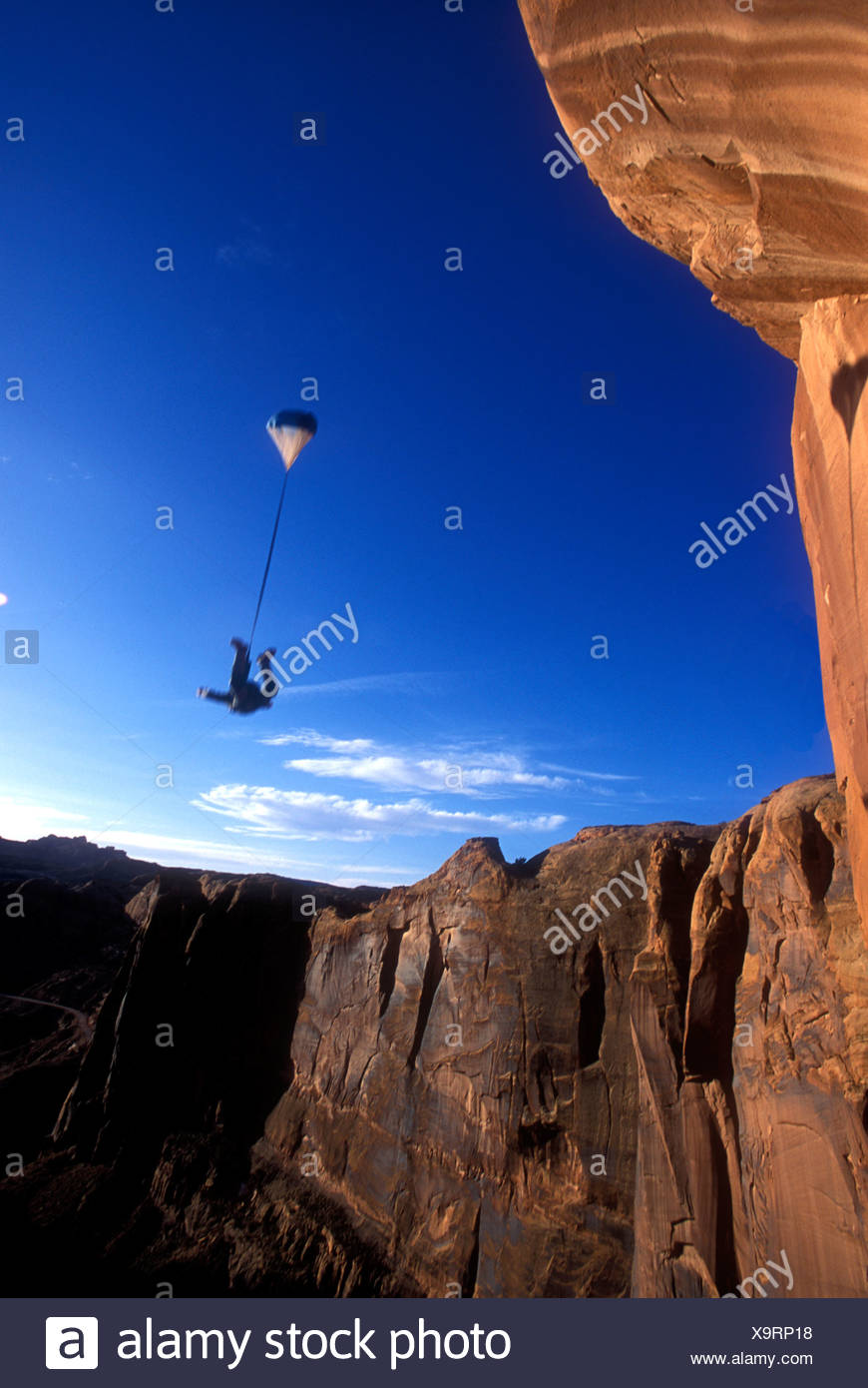 Man base jumping off the Tombstone, Utah, USA. - Stock Image