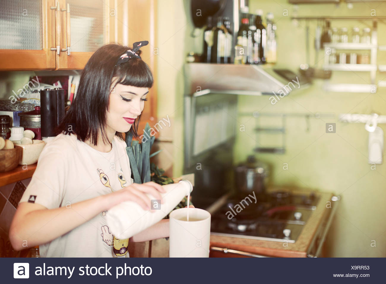 Young woman preparing a milk drink in kitchen - Stock Image