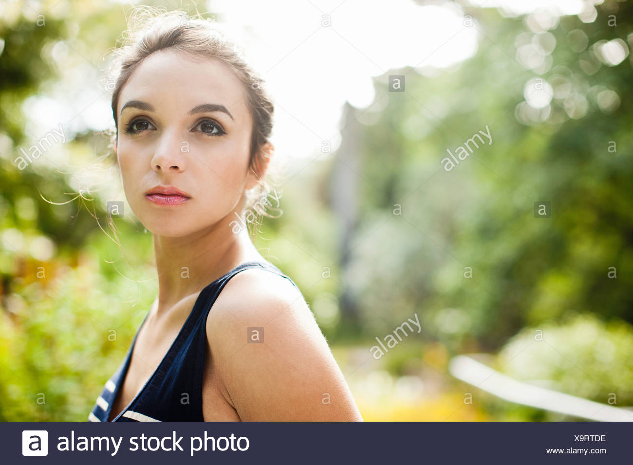 Young woman looking away, close up - Stock Image