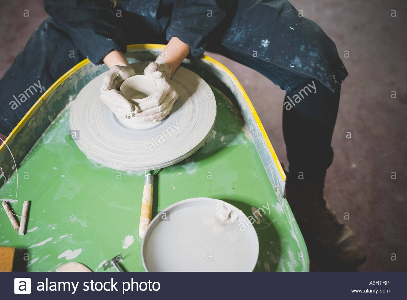 High angle view of young woman, waist down, sitting at pottery wheel making clay pot Stock Photo