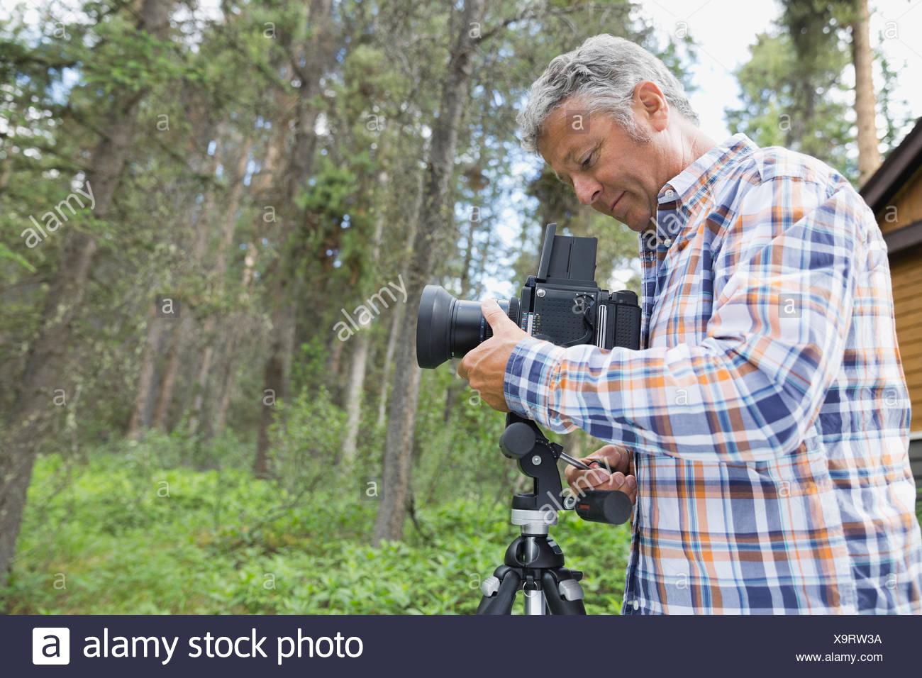 Man adjusting lens of SLR camera in yard - Stock Image