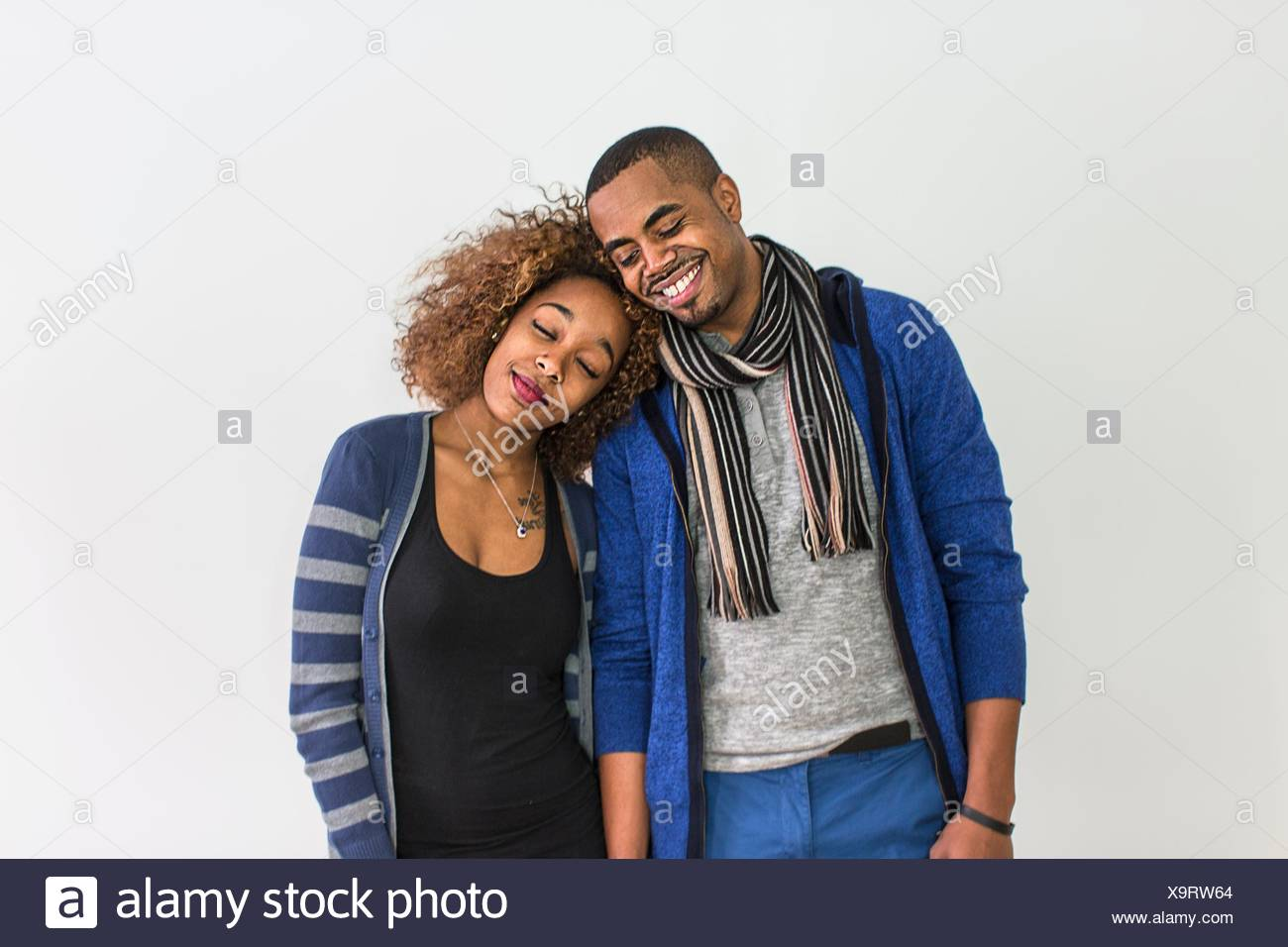 Studio portrait of romantic couple with heads on each others shoulder - Stock Image