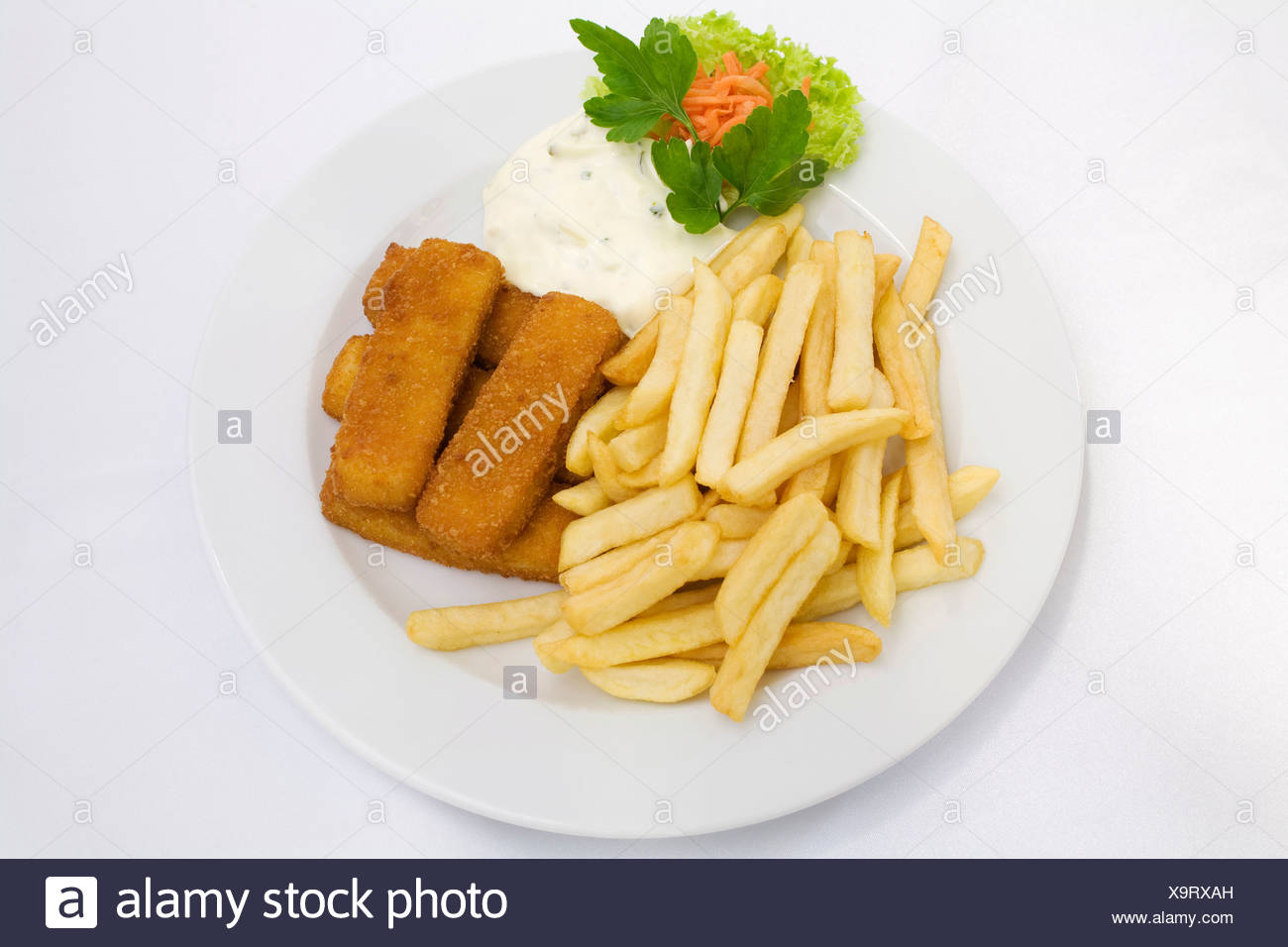 Fish sticks, tartar sauce and french fries served on a white plate - Stock Image
