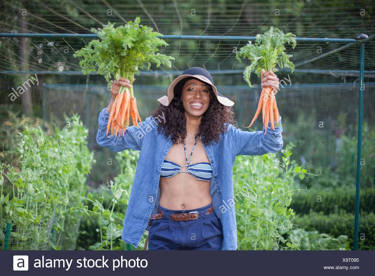 Woman holding up carrots from allotment - Stock Image
