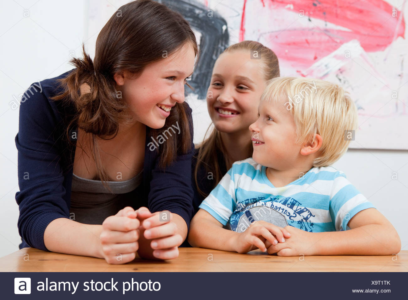Brother and sisters at table - Stock Image