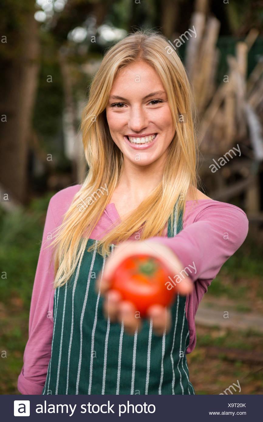 Portrait of happy gardener offering fresh tomato at garden - Stock Image
