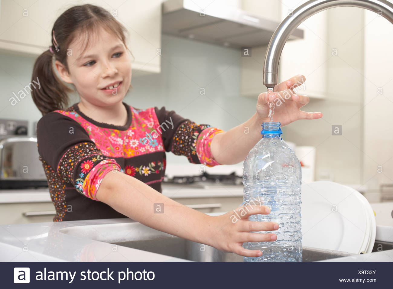 Girl filling up water bottle in kitchen Stock Photo