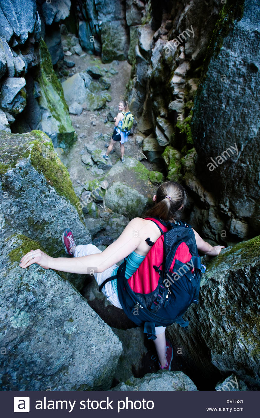 Two women climb through Crack In the Ground, a volcanic fissure near Christmas Valley, Oregon. - Stock Image