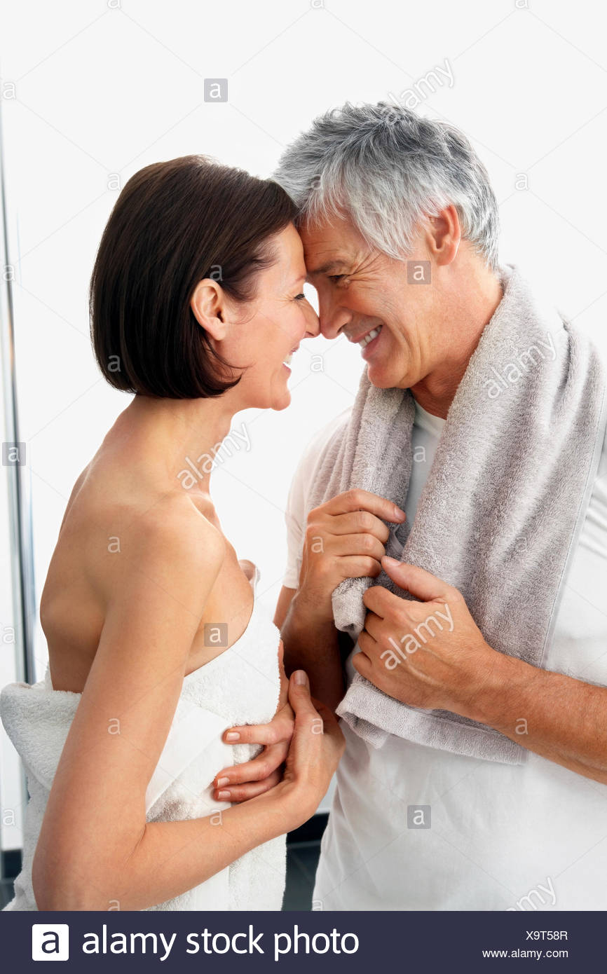 Happy couple with towels head to head in front of white background - Stock Image