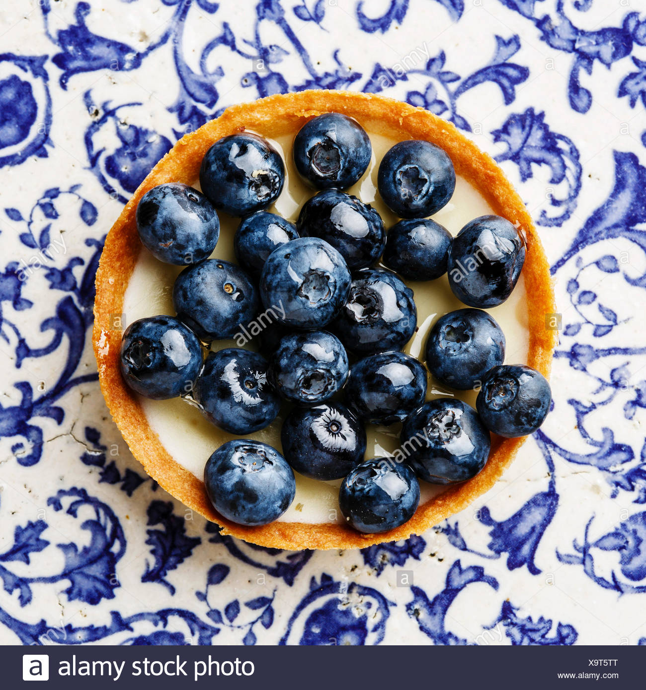 Blueberry tart on blue ornament background - Stock Image
