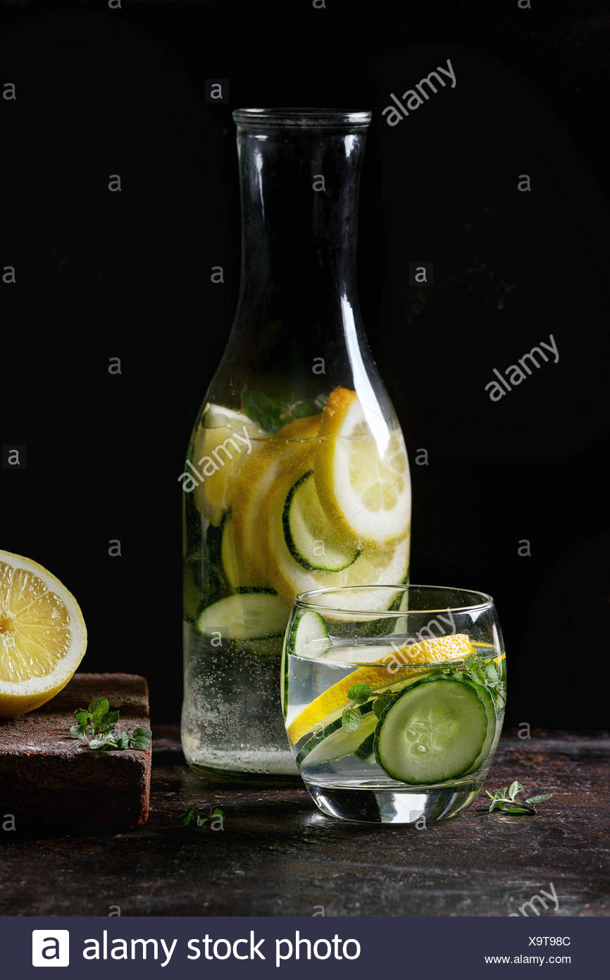 Citrus cucumber sassy sassi water for detox in glass bottle on dark black background. Clean eating, healthy lifestyle concept, sunlight - Stock Image